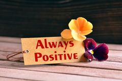 Always positive tag. Tag banner always positive and violet flower on wooden desk Royalty Free Stock Photography