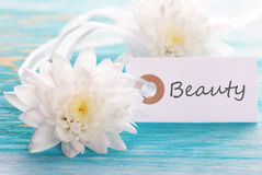 Tag with Beauty. On a turquoise Board with White Blossoms Stock Images