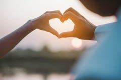 Tag der Liebe der jungen Hand mit dem Herzen von zwei Leuten Stockfotos