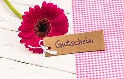 Flower blossom with gift card with german word, Gutschein, means voucher or coupon. Tag with german word, Gutschein, means voucher or coupon and beautiful pink Royalty Free Stock Photo