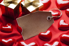 Tag, gift boxes and red hearts Royalty Free Stock Photography