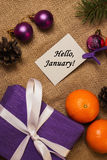 Tag Hello January, purple gift with postcard, orange tangerines Stock Photo