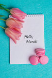 Tag hello march with three pink tulips and three pink macaroons stock photos