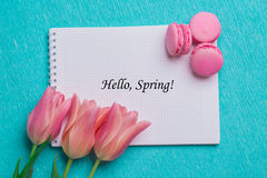 Tag hello spring with three pink tulips and three pink macaroons stock photography