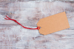 Tag of kraft paper on light gray wooden background Royalty Free Stock Photos