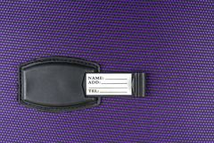 The tag on the Luggage to provide the name and phone number on a purple fabric royalty free stock photo