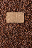 Tag made of burlap lies against the backdrop of  coffee beans. With place for your creativity Royalty Free Stock Photos