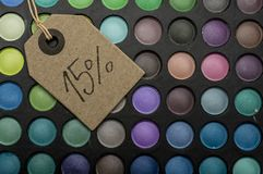 15 percent off in makeup. Tag placed on colorful makeup palettes writing 15 percent discount Stock Photography