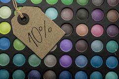10 percent off in makeup. Tag placed on colorful makeup palettes writing 10 percent discount Royalty Free Stock Photography
