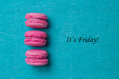 Tag It's friday with three pink macaroons. On blue background stock image