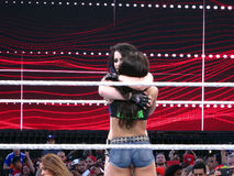 Tag team partners AJ Lee and Paige hug after match at Wrestleman Royalty Free Stock Photos