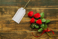 Tag template next to a red bouquet of roses. On a rustic wood background stock photo