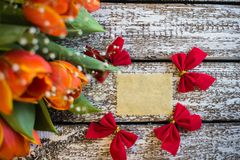 A tag on a wooden background with tulips.  Royalty Free Stock Photo