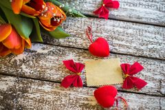 A tag on a wooden background with tulips.  Royalty Free Stock Photos