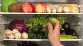 Tagande för ung kvinna ut ur kylskåpgurkan stock video