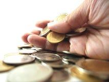 Tagandemynt i handen, hög av pengar Arkivbilder