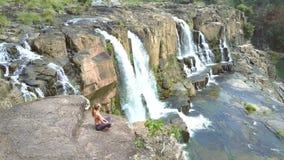 Tagandeplatsen för flickan barfota vaggar på på vattenfallnivån stock video