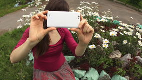 Tagandeselfie för ung kvinna vid den vita telefonen, medan sitta på blommande tusenskönor stock video