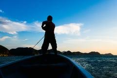 TAGANGA,哥伦比亚- 2017年10月19日:未认出的人的阴影在一条小船里面的在美丽的日落期间 库存图片