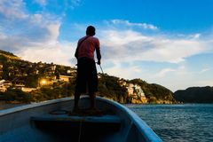 TAGANGA, COLOMBIA - OCTOBER 19, 2017: Shadow of unidentified man inside of a boat during a sunset at the beautiful. Caribbean beach in Taganga, Colombia stock photo