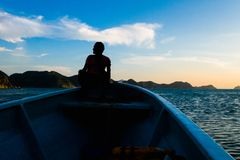 TAGANGA, COLOMBIA - OCTOBER 19, 2017: Shadow of unidentified man inside of a boat during a sunset at the beautiful. Caribbean beach in Taganga, Colombia stock image