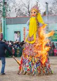Maslenitsa celebration. Man sets fire to a big doll-scarecrow on a stage in a city park stock images