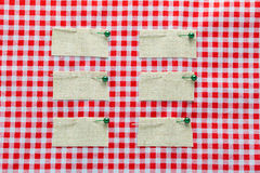 Tagaufkleber auf quadratischem rotem Gewebe Lizenzfreie Stockbilder