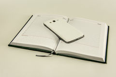Tagebuch auf einem weißen Hintergrund und einem Smartphone, die auf ihm liegen Stockfoto