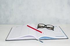 Tagebuch, Gläser und ein Bleistift Stockfotos