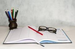 Tagebuch, Gläser und ein Bleistift Lizenzfreies Stockbild