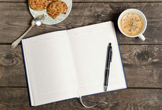 Tagebuch mit einem Stift, einem Kaffee und einer Untertasse mit Plätzchen auf einem hölzernen ta Lizenzfreies Stockbild
