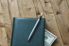 Tagebuch, Stift und Teil einer Rechnung auf einer Holzoberfläche Lizenzfreie Stockbilder