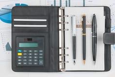 Tagebuch, Taschenrechner und drei sperren das Lügen auf einem Hintergrund des Diagramms ein Stockbild