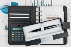 Tagebuch, Taschenrechner und Stift im Kasten auf einem Hintergrund von Diagrammen Lizenzfreie Stockfotos