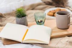 Tagebuch, Tee und Kerze im Halter zu Hause Stockbilder