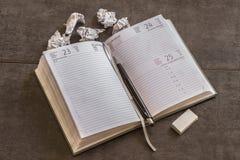 Tagebuch und Stift liegen neben zerknitterten Blättern Papier Lizenzfreie Stockbilder
