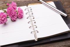 Tagebuchanmerkung mit Rosarose auf altem Holz Lizenzfreie Stockfotografie