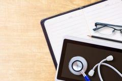 Tagebuchplanerbuch im schwarzen Leder und im Stethoskop Lizenzfreie Stockfotografie
