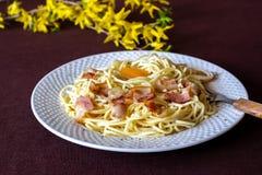 tagen bild f?r pasta f?r carbonaradaglampa Blommor i bakgrunden italienska matlagningmatingredienser arkivbild