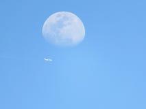 Tagesmond mit Flugzeugfliegen unten Stockbild