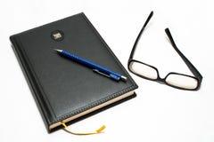 Tagesordnung mit Feder und Gläsern Lizenzfreie Stockfotos