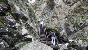 Tagesschuß von den Leuten, die oben hölzerne Treppe, draußen durch die Berge laufen lassen stock video footage
