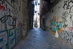 Tagged walls. On a narrow and dark paved street in Naples, Campania, Italy stock image