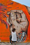 Taggers and Graffiti artist at work making vibrant artworks Stock Photo