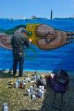 Taggers- und Graffitikünstler bei der Arbeit, die vibrierende Grafiken macht Stockbild