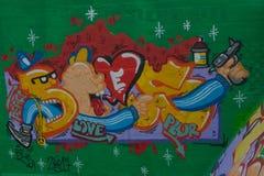 Taggers- und Graffitikünstler bei der Arbeit, die vibrierende Grafiken macht Lizenzfreie Stockbilder