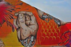 Taggers- und Graffitikünstler bei der Arbeit, die vibrierende Grafiken macht Stockfotografie
