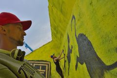 Taggers- und Graffitikünstler bei der Arbeit, die vibrierende Grafiken macht Lizenzfreies Stockbild