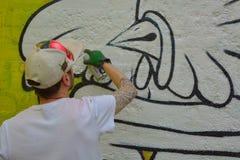 Taggers- und Graffitikünstler bei der Arbeit, die vibrierende Grafiken macht Lizenzfreie Stockfotos