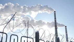 Taggtråd som ett symbol av mänsklighet i gisslan av prorgess förorening för fabrik för luftbakgrund blå Global uppvärmningproblem stock video